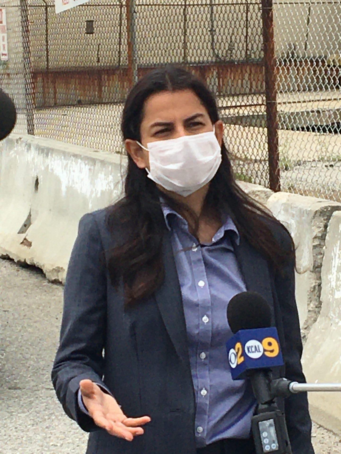 Congresswoman Barragan speaks to reporters wearing a mask